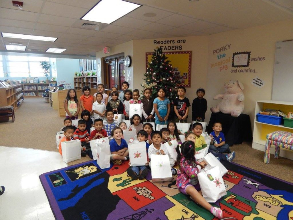 group photo of children holding gifs for holiday toy drive