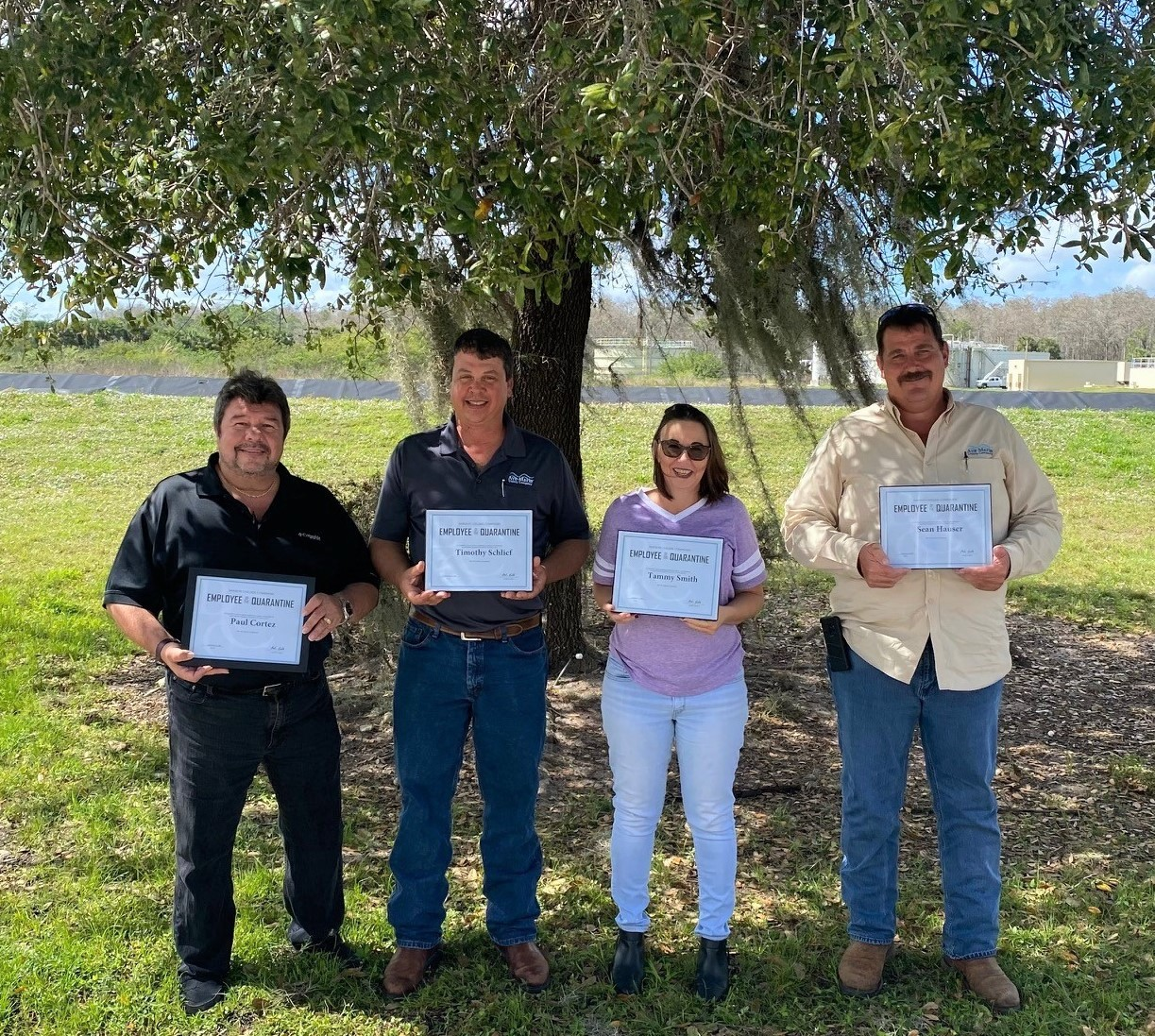 Four people standing holding certificates outdoors