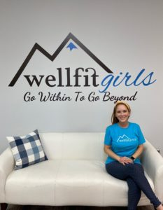 Girl sitting on couch with Wellfit Girls logo behind her